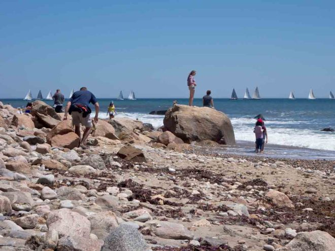 Beach with lots of people and racing sail boats
